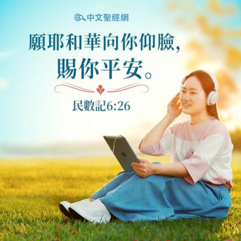 基督徒坐在草地上拿著平板聽詩歌