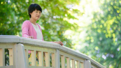 基督徒面帶微笑站在橋欄邊