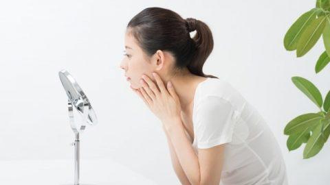 女子照着鏡子很在乎自己的皮膚
