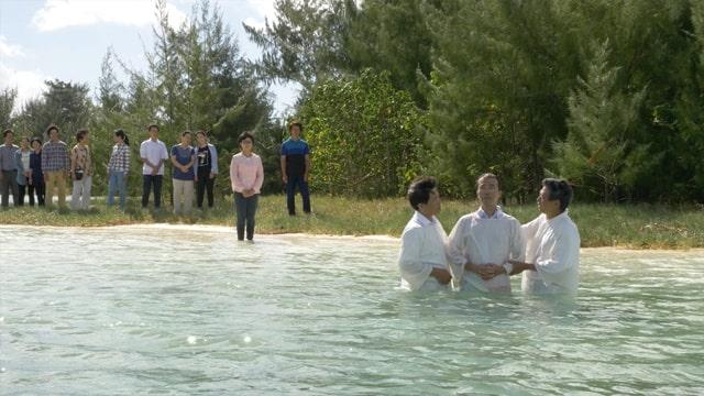 基督徒站在河裡受洗,還有一些基督徒站在河岸等待受洗