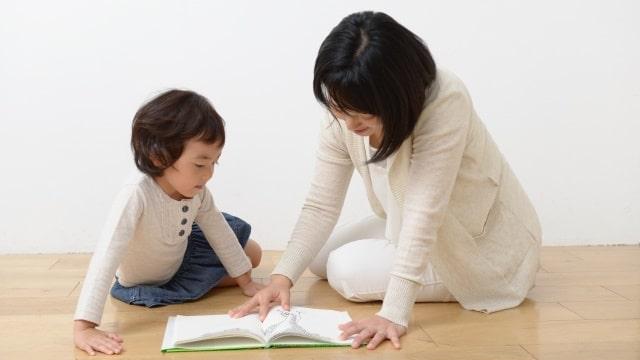 家庭老師在認真地教小孩子看圖識字