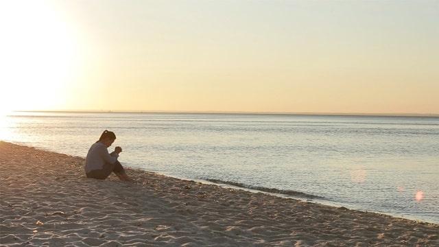 她坐在海邊禱告