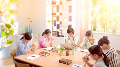 幾個姊妹圍坐在一起禱告神,桌子上有神的話語