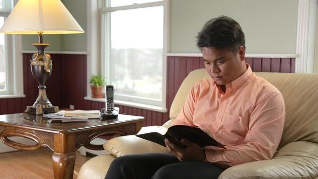 清晨讀坐在沙發上讀神的話語