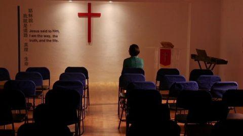 她獨自坐在椅子上呆呆地望着十字架