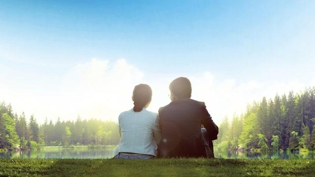 夫妻平靜而幸福地坐在草地上聊天