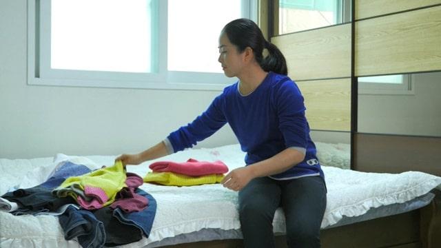 她坐在床邊整理衣服