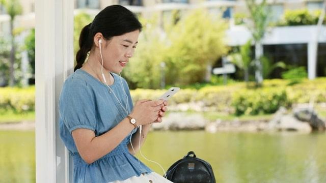 她坐在涼亭面帶微笑地拿著手機