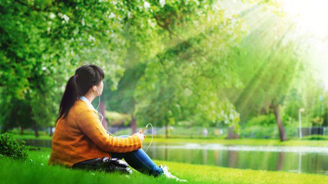 女孩獨自坐在草地上聽着音樂享受着陽光的撫慰