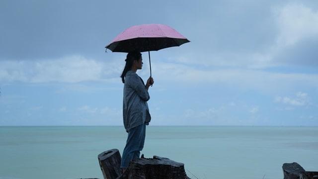 一個女人打着傘站在海邊,心情很沉重