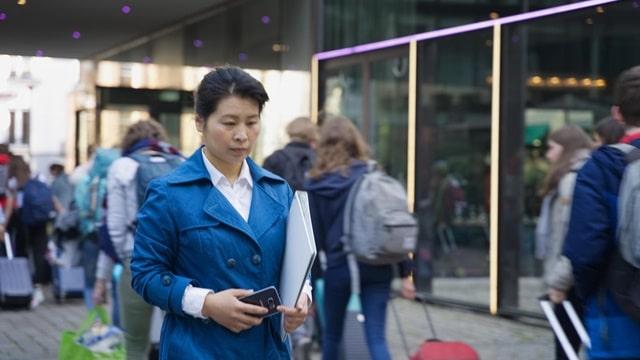 她拿着手機沉重地走在道上