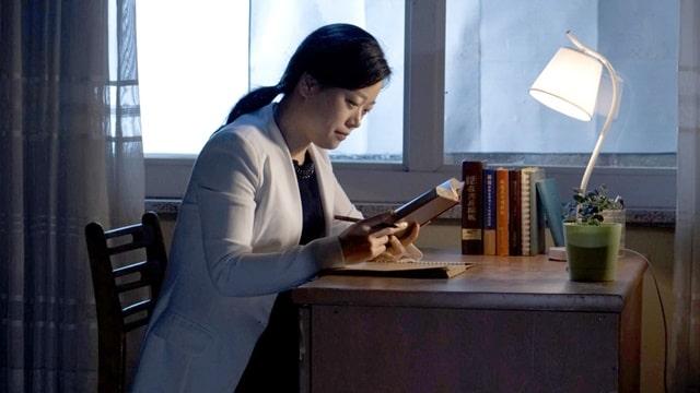 她夜晚獨自坐在窗前的書桌旁看神的話語