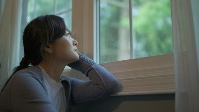 一副愁苦的表情看着窗外
