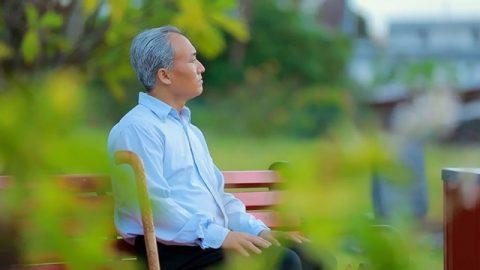 一位老年人坐在公園的長椅上思考