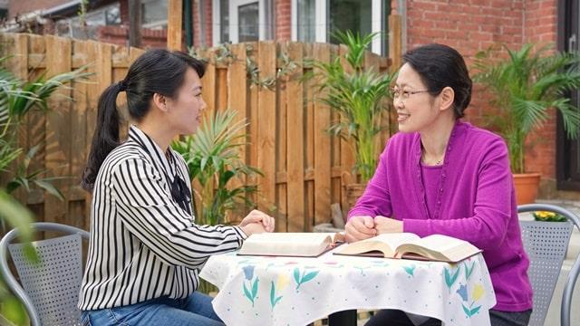兩個姊妹圍坐在院子裏的桌子交談