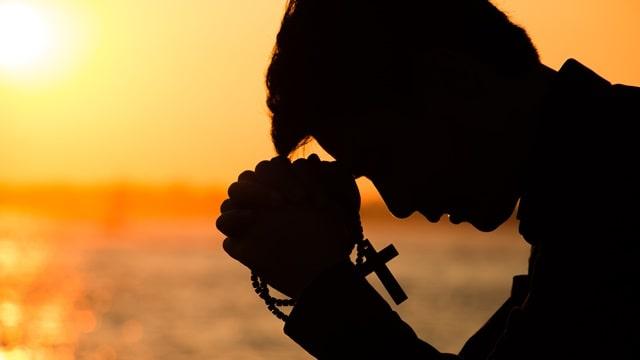 手拿十字架坐在海邊禱告