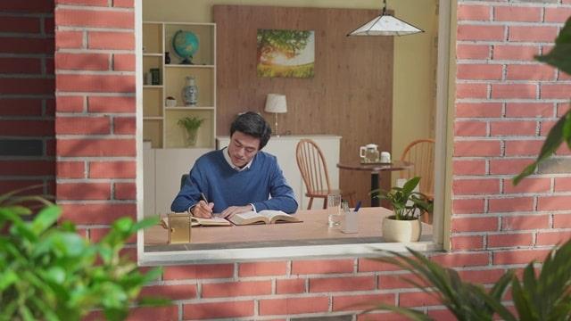 他坐在窗前寫信