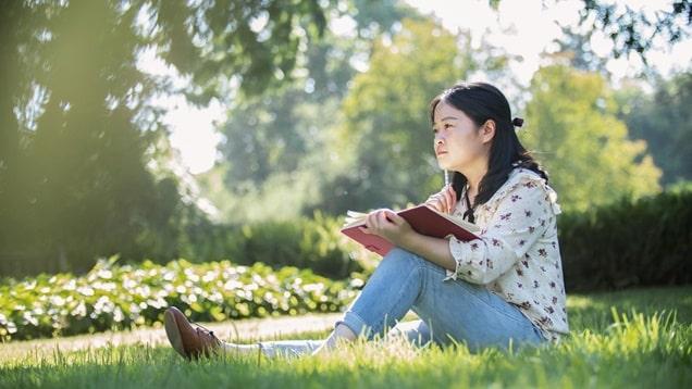 坐在草地上拿着書本思考問題