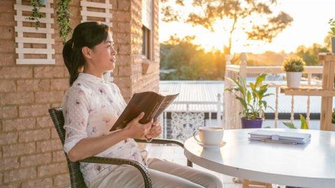 陽光普照的早上,她坐在陽臺上手拿神話面帶笑容