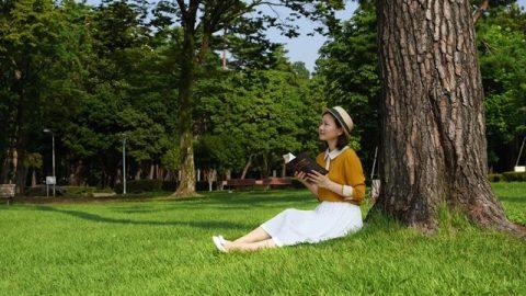 坐在樹下手拿着神話語書籍,臉面露出笑容